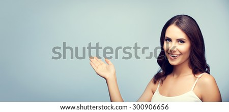 Portrait of cheerful smiling young woman in white tank top clothing, showing copyspace or something - stock photo