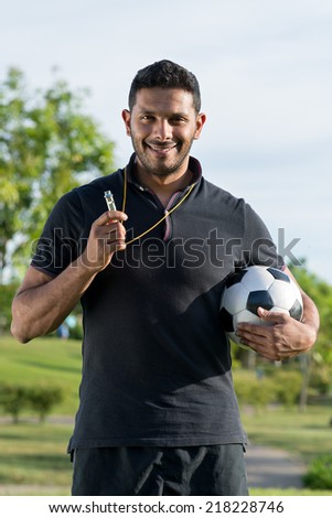 Portrait of cheerful soccer coach holding a ball - stock photo