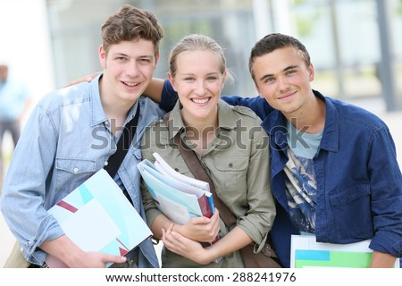 Portrait of cheerful students holding books - stock photo
