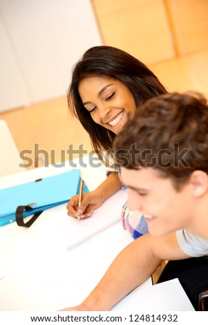 Portrait of cheerful students in class - stock photo