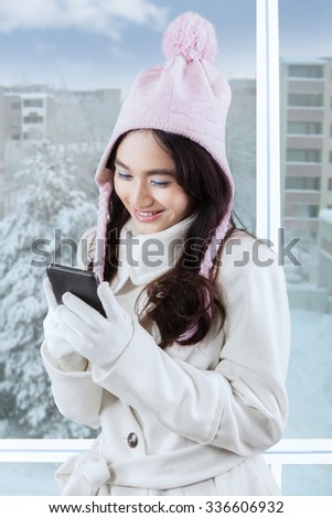 Portrait of cheerful teenage girl wearing winter fashion and texting with a mobile phone near the window - stock photo
