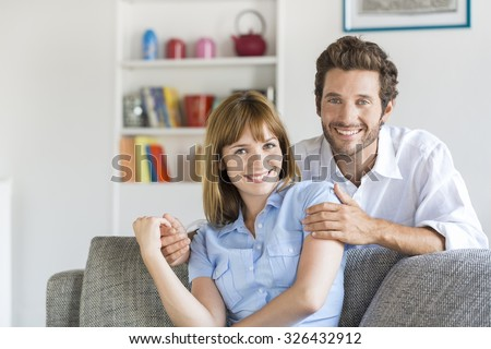 Portrait of cheerful thirty year old couple sitting on sofa in modern white apartment - stock photo