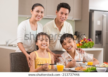 Portrait of cheerful Vietnamese family in the dining room - stock photo