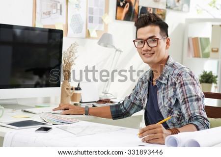 Portrait of cheerful Vietnamese interior designer at work - stock photo