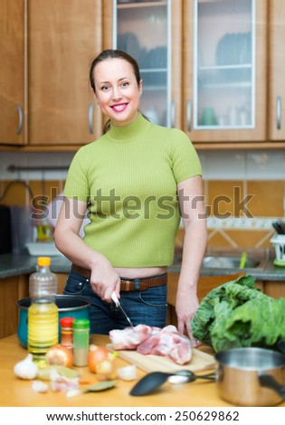 Portrait of cheerful woman cooking dinner at home kitchen - stock photo
