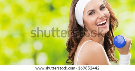 Portrait of cheerful woman in fitness wear exercising with dumbbell, outdoors, with copyspace - stock photo