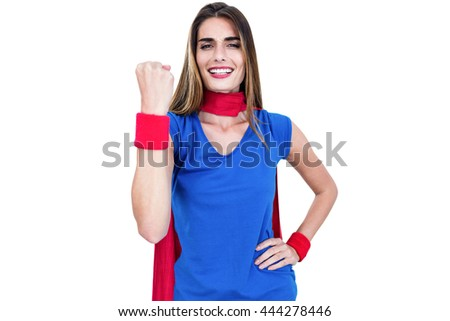 Portrait of cheerful woman in superhero costume while standing on white background - stock photo