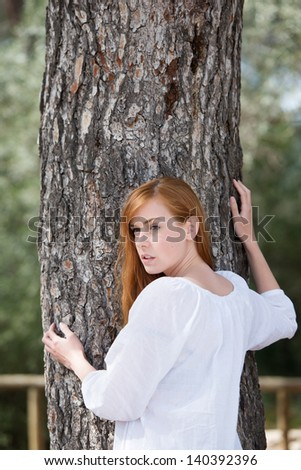 Portrait of cheerful woman posing with a big tree trunk - stock photo