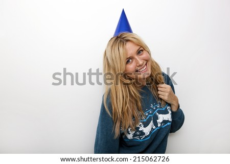 Portrait of cheerful woman wearing party hat against white background - stock photo