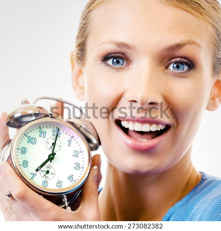 Portrait of cheerful woman with alarmclock, over grey background - stock photo