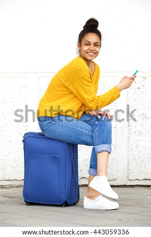 Portrait of cheerful young african woman sitting on travel bag with mobile phone - stock photo
