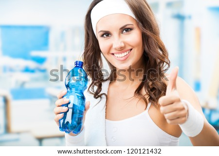 Portrait of cheerful young attractive woman showing thumbs up gesture, with bottle of water, at fitness club or gym - stock photo
