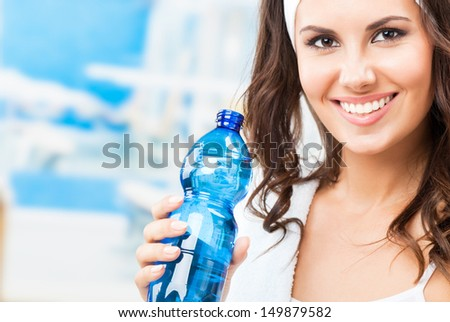 Portrait of cheerful young attractive woman with bottle of water, at fitness club or gym - stock photo