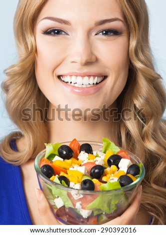 Portrait of cheerful young beautiful blond woman with vegetarian salad, against blue background. Healthy eating and diet concept. - stock photo