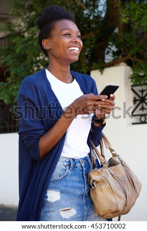 Portrait of cheerful young black woman walking down the street with cell phone
