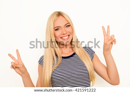 Portrait of cheerful young blonde gesturing with two fingers - stock photo