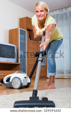 Portrait of cheerful young blonde housewife vacuuming in living room - stock photo