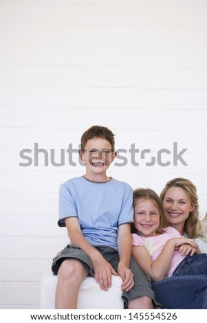 Portrait of cheerful young boy with mother and sister sitting on sofa at home - stock photo