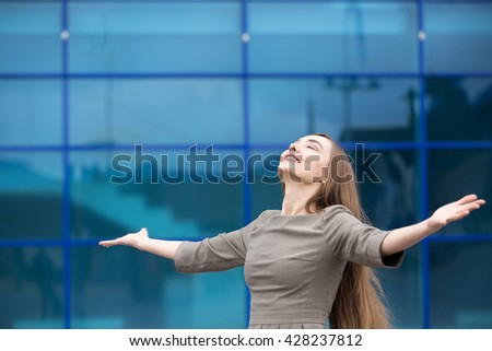 Portrait of cheerful young business woman standing with outstretched arms and relaxing outdoors with closed eyes. Happy beautiful caucasian woman feeling ecstatic on the street in summer. Copy space - stock photo
