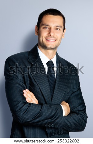 Portrait of cheerful young businessman with crossed arms pose, against grey background - stock photo