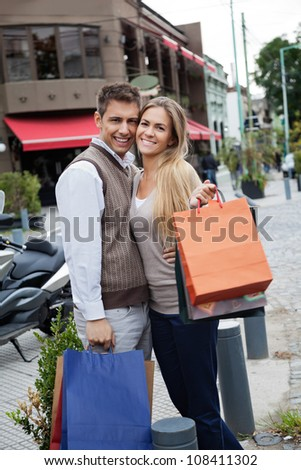 Portrait of cheerful young couple with shopping bags standing on sidewalk - stock photo