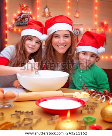 Portrait of cheerful young family preparing to Christmas dinner, mother with two kids cooking at home wearing Santa hat - stock photo