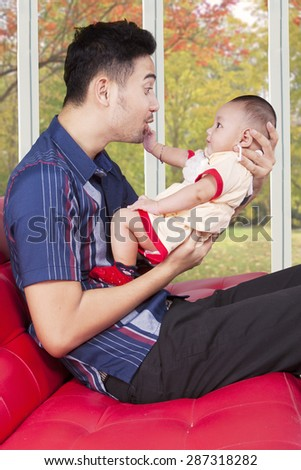 Portrait of cheerful young father sitting on the sofa while playing with his baby, shot with autumn background on the window - stock photo