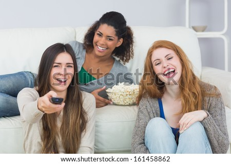 Portrait of cheerful young female friends with remote control and popcorn bowl on sofa at home - stock photo