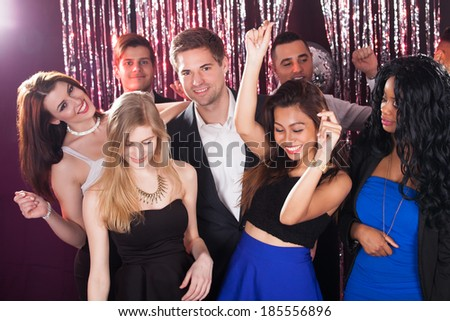 Portrait of cheerful young friends dancing in nightclub - stock photo