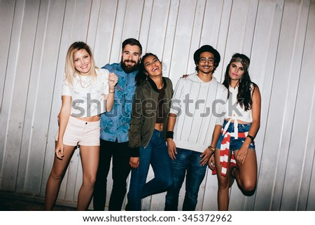 Portrait of cheerful young friends standing together outdoors. Multiracial young people hanging out at night. - stock photo