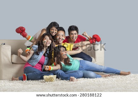 Portrait of cheerful young friends watching a boxing match together at home - stock photo