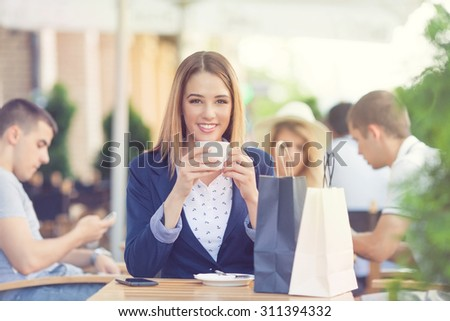 Portrait of cheerful young girl drinking coffee and relaxing in an outdoor cafe after shopping - stock photo