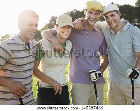 Portrait of cheerful young golfers on golf course - stock photo