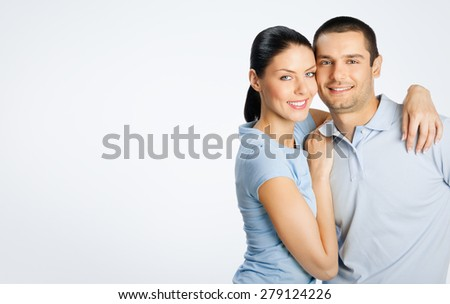 Portrait of cheerful young lovely couple, with copyspace blank area for text or slogan, on grey background - stock photo