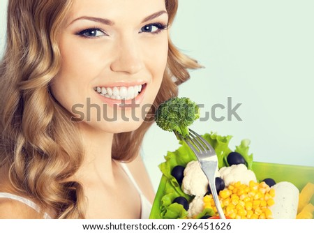 Portrait of cheerful young lovely woman with healthy vegetarian salad with broccoli, against blue background. Healthy eating and dieting concept. - stock photo