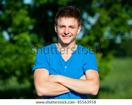 portrait of cheerful young man in blue t-shirt - stock photo
