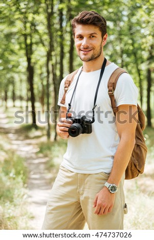 Portrait of cheerful young man photographer with modern photo camera in forest