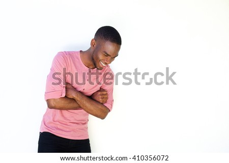 Portrait of cheerful young man standing against white background and looking down - stock photo
