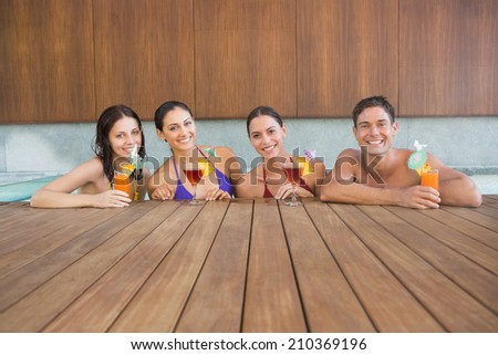 Portrait of cheerful young people with drinks in the swimming pool - stock photo