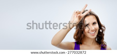 Portrait of cheerful young woman in smart casual violet clothing, showing two fingers or victory gesture, over grey background, with blank copyspace area for slogan or text. Selective focus on hand. - stock photo