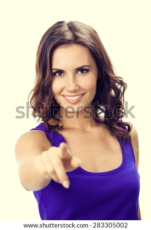 Portrait of cheerful young woman in violet smart casual clothing, pointing at something over her finger or pressing virual button - stock photo