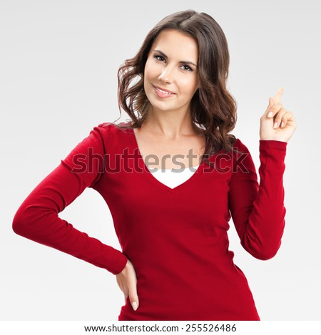 Portrait of cheerful young woman showing copyspace, visual imaginary or something, or pressing virual button, over grey background - stock photo