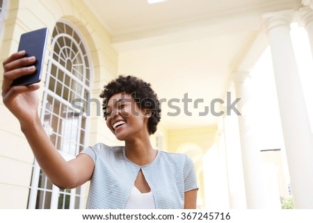 Portrait of cheerful young woman taking a selfie with her mobile phone outdoors  - stock photo