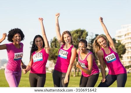 Portrait of cheering women supporting breast cancer marathon in parkland - stock photo