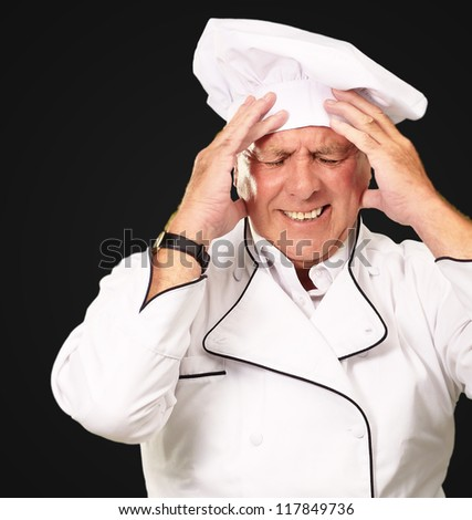 Portrait Of Chef With Painfully Head On Black Background - stock photo