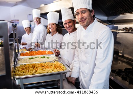 Portrait of chefs standing at serving trays of pasta in commercial kitchen - stock photo