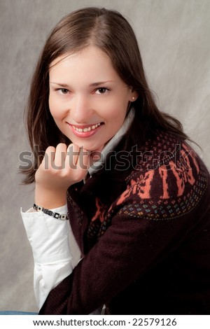 portrait of chestnut head girl wearing sweater sitting in half-turn with hand near face smiling - stock photo