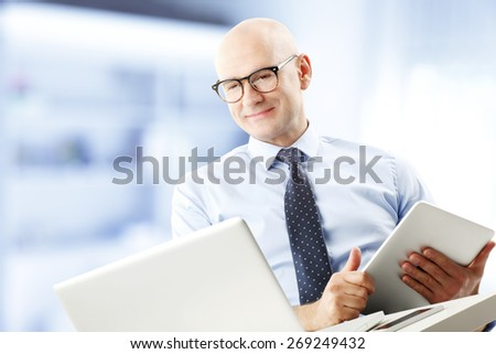 Portrait of chief financial officer holding financial report in hands while sitting in front of laptop and analyzing data. Businessman working at office.  - stock photo