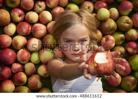 Portrait of child blond little cute girl lying on the grass showing apple with apples background