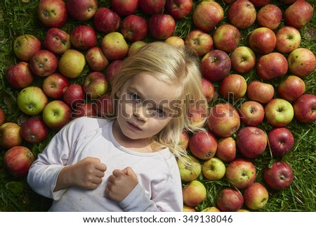Portrait of child blond little girl with pile of apples background lying on green grass lawn